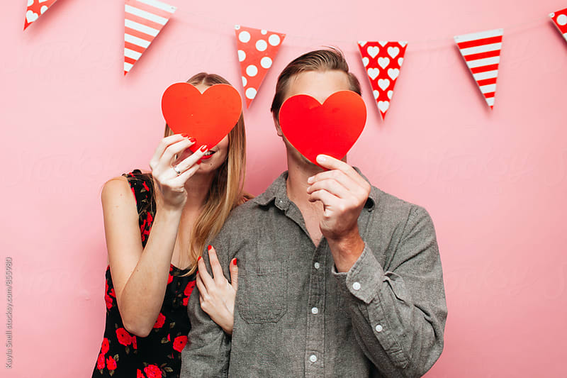 Young couple with hearts in front of their faces by Kayla Snell for Stocksy United