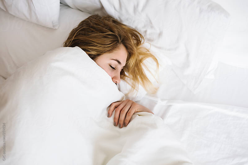 Young woman sleeping in the bed by Simone Becchetti for Stocksy United
