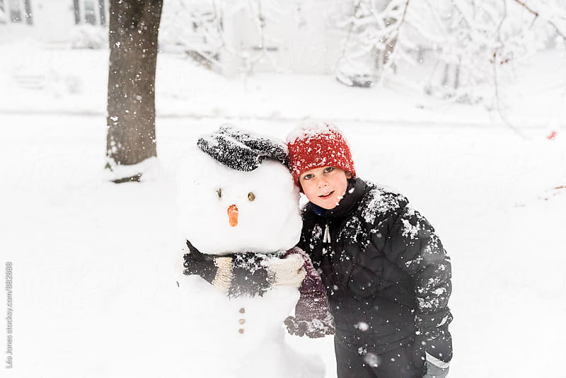 little boy standing byes snowman by Léa Jones for Stocksy United