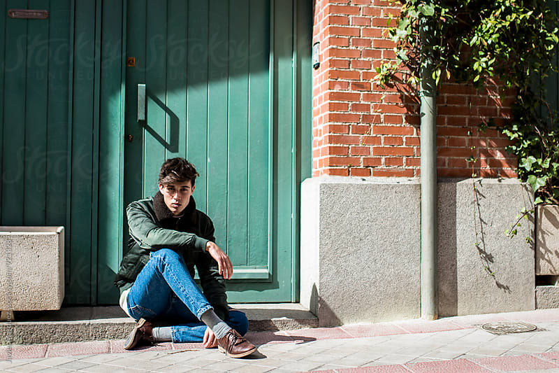 Young man sitting on a door by Javier Márquez for Stocksy United