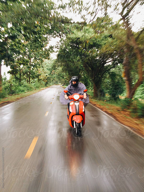 Young man rides moto in rain  by Jesse Morrow for Stocksy United