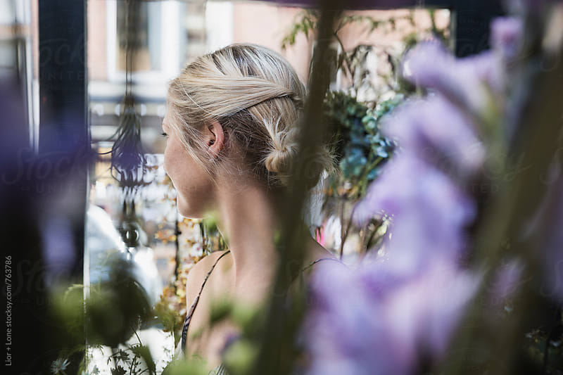 Blond woman looking away shot through purple flowers by Lior + Lone for Stocksy United
