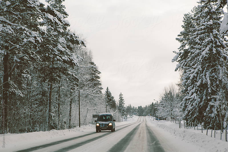 A lone car driving down a snowy Swedish road by Stephen Morris for Stocksy United