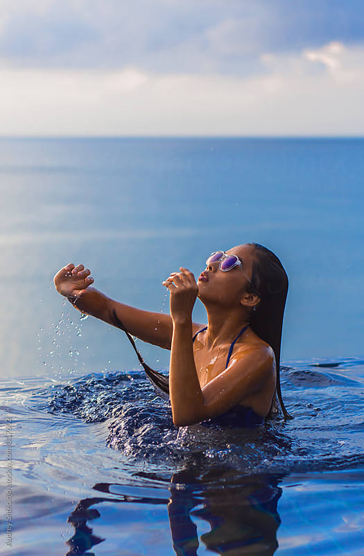 Sensual Asian Woman with sunglasses at the swimming pool relaxing during sunset. by Audrey Shtecinjo for Stocksy United