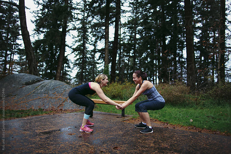Two caucasion female friends working out together at wet outdoor boot camp by Rob and Julia Campbell for Stocksy United