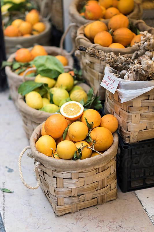 Baskets of oranges and lemons outside a store by Luca Pierro for Stocksy United
