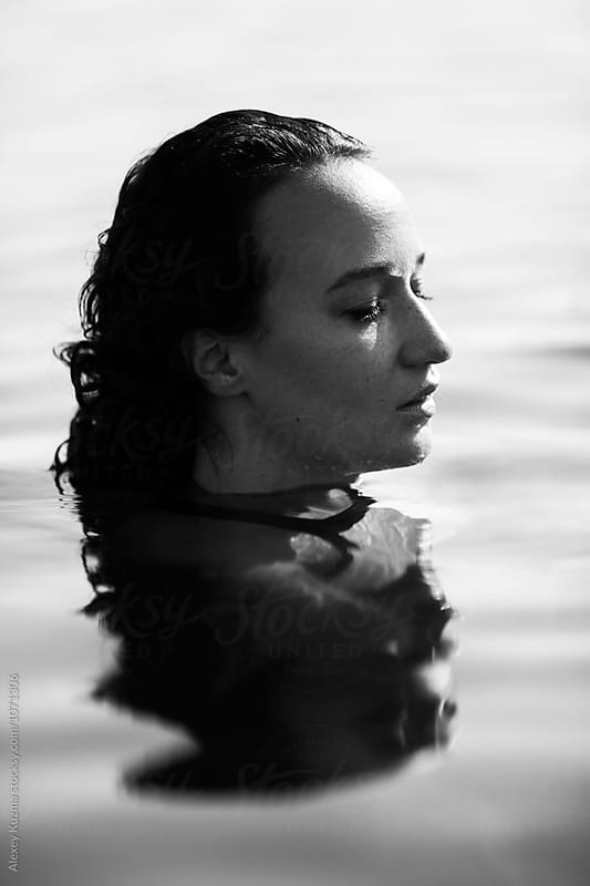 portrait of young woman in the water by Alexey Kuzma for Stocksy United