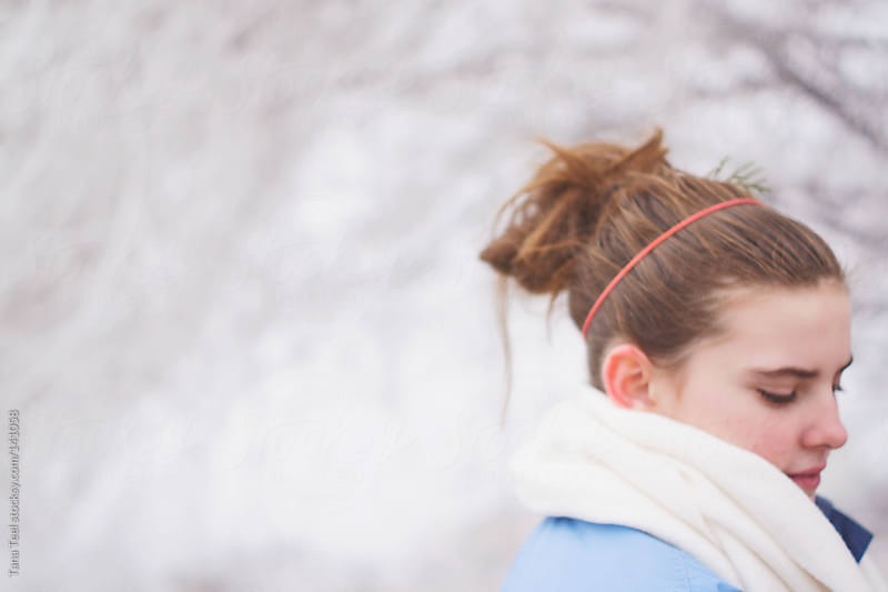 A teenage girl wrapped in a scarf  pauses on a walk on a winter day by Tana Teel for Stocksy United