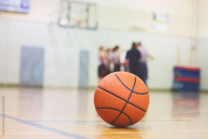 A basketball sits on a court before a game by Tana Teel for Stocksy United