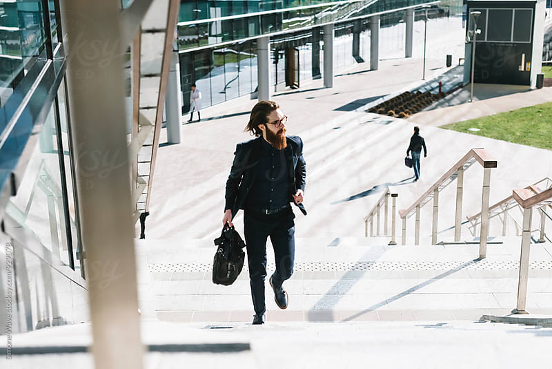 Businessman walking in the city by GIC for Stocksy United