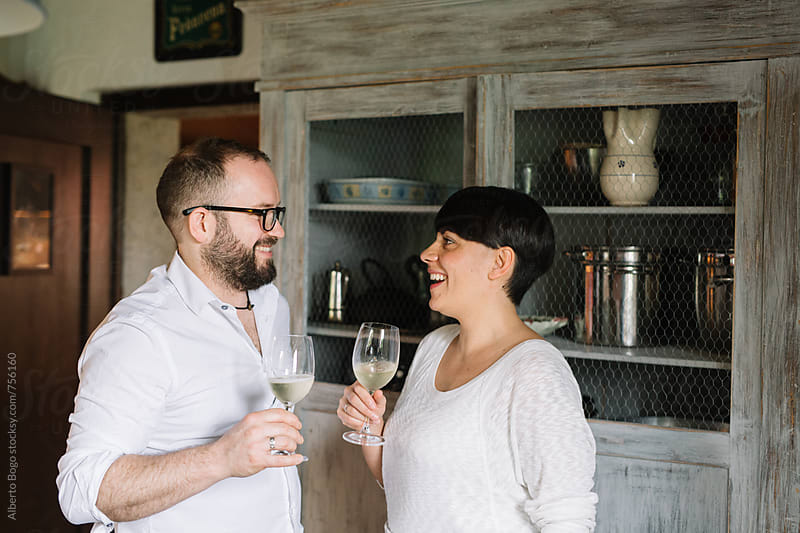 Smiling couple drinking wine together at home by Alberto Bogo for Stocksy United