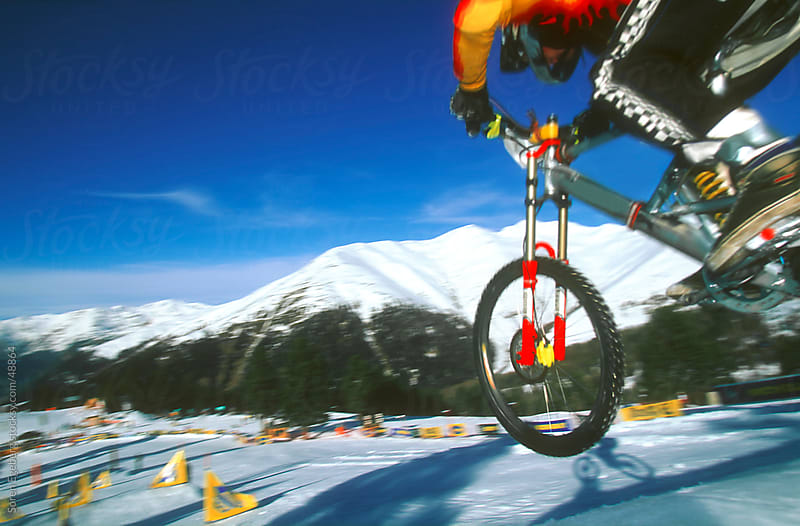 Mountain biker jumping on snow slope in mountains at ski resort in winter by Soren Egeberg for Stocksy United