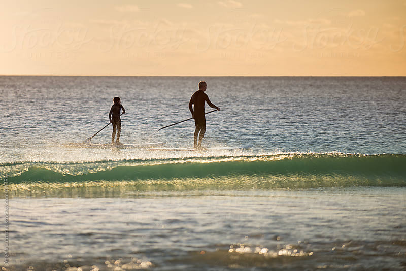 Father and son stand up paddling together at sunset by Angela Lumsden for Stocksy United