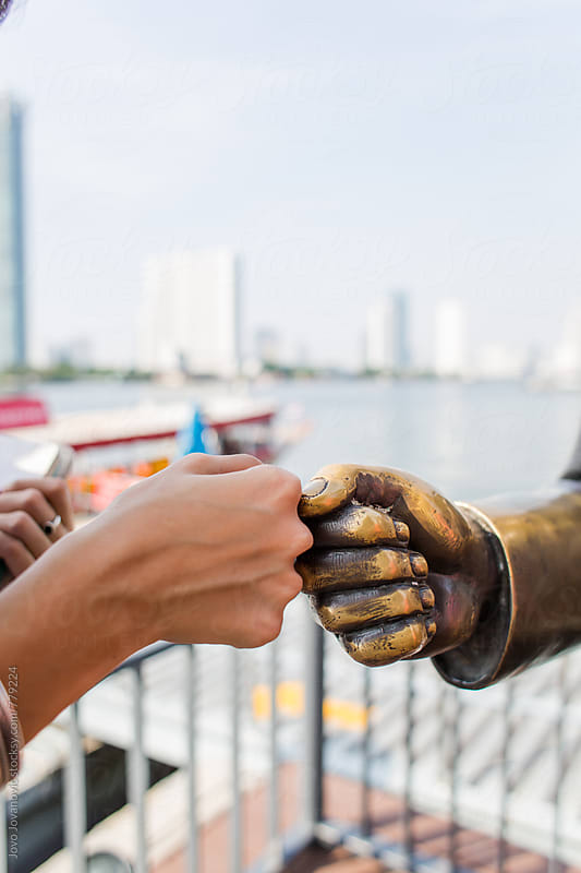 Fist bumping a statue by Jovo Jovanovic for Stocksy United