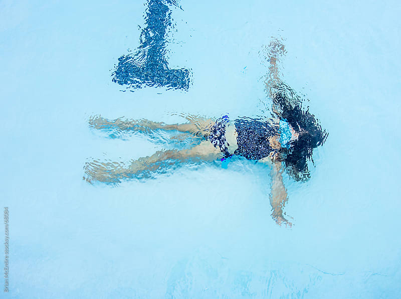 Child Under Water At Bottom of Swimming Pool by Brian McEntire for Stocksy United