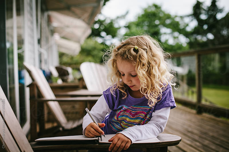 A little girl reads and writes. by Cherish Bryck for Stocksy United
