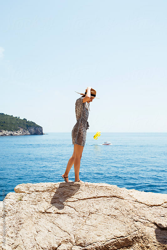 Woman standing on a cliff by Maja Topcagic for Stocksy United