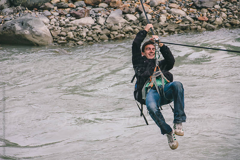 Young man on a canopy or zipline crossing a river on adventure travel by Alejandro Moreno de Carlos for Stocksy United