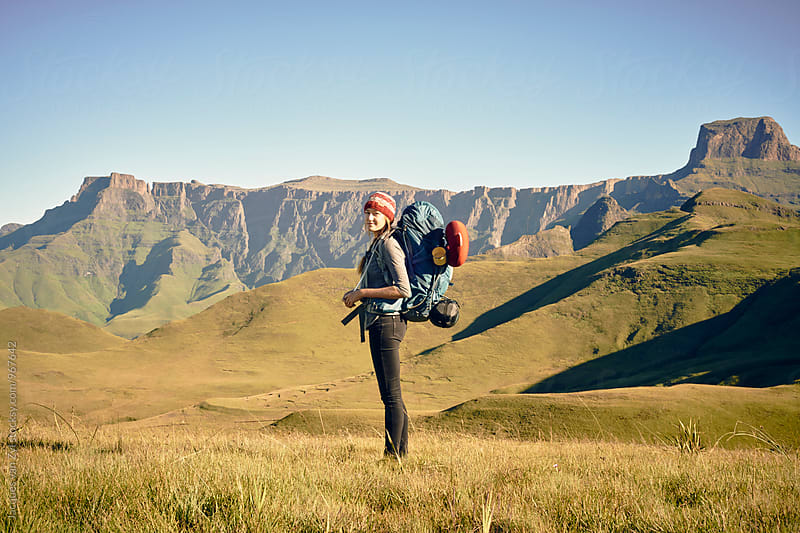 Female hiker with back pack standing  in front a big mountain. by Jacques van Zyl for Stocksy United