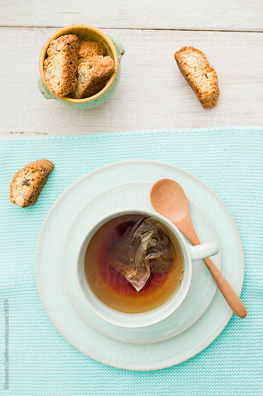 Light turquoise cup with tea and a teabag on a plate and biscotti on the side by Elisabeth Coelfen for Stocksy United