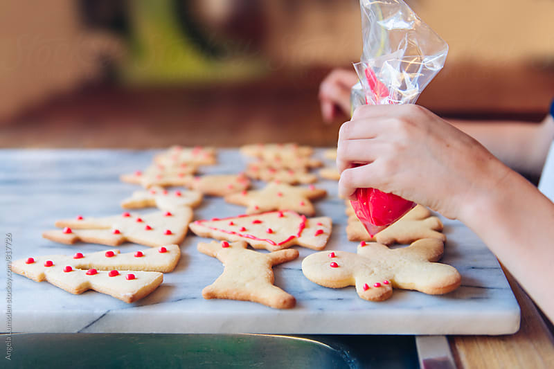 Child decorating christmas cookies with a bag of red icing by Angela Lumsden for Stocksy United