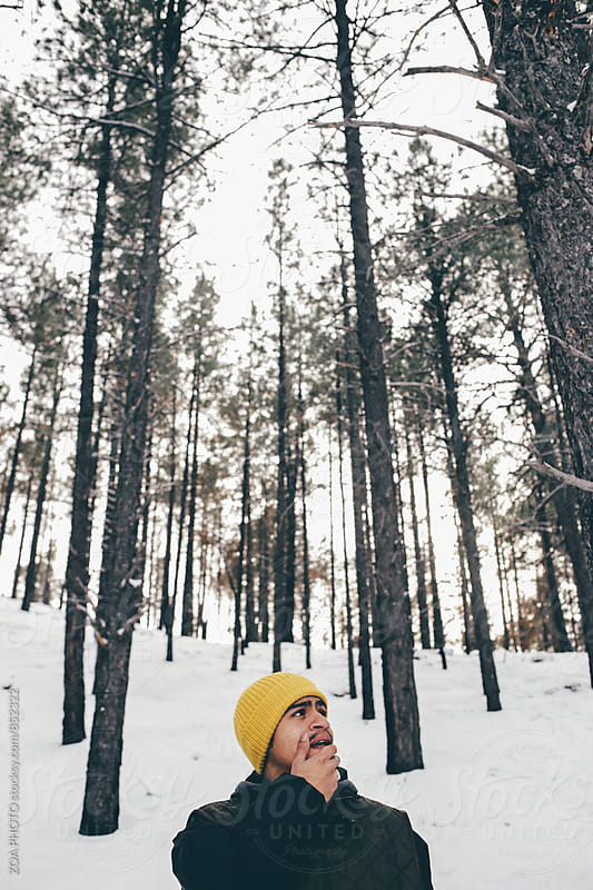 Man looking up in wooded snowy area by ZOA PHOTO for Stocksy United