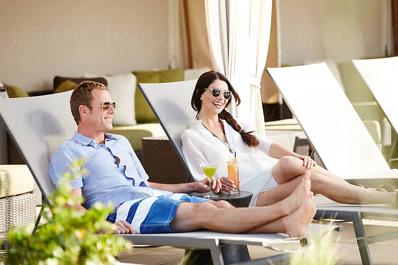 Couple relaxing by pool at luxury resort cabanas.  by Trinette Reed for Stocksy United