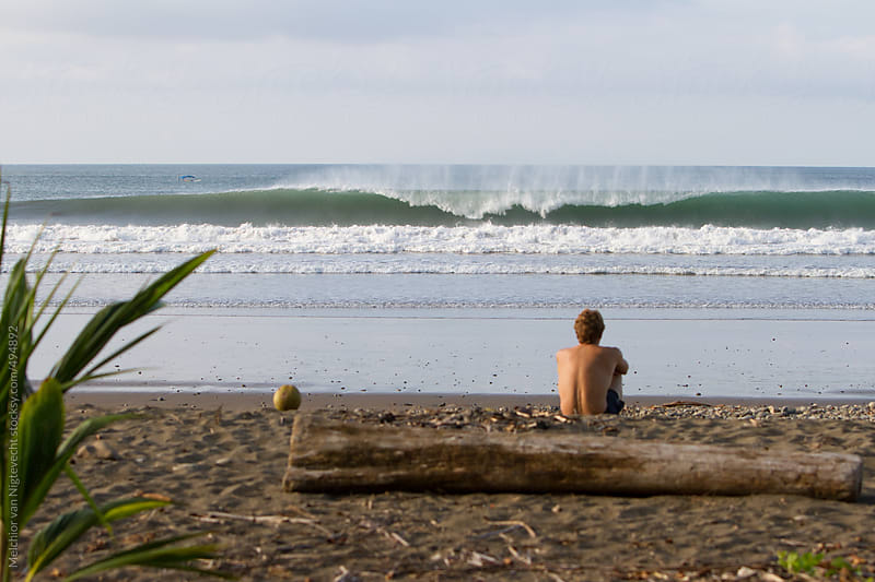 Young man watching a wave breaking by Melchior van Nigtevecht for Stocksy United
