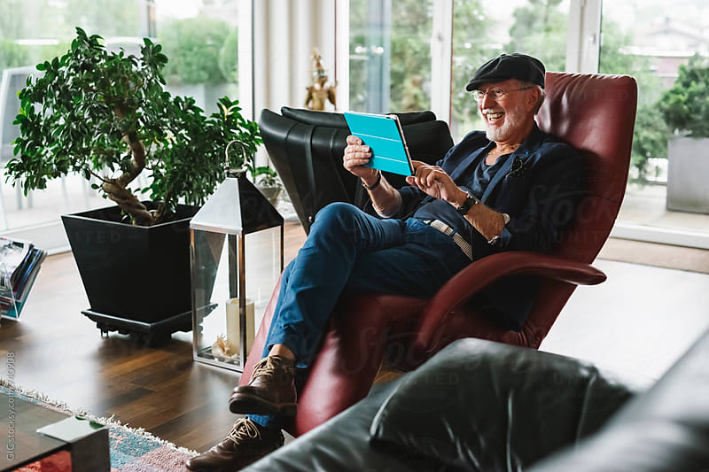 Happy and active senior man using a digital tablet at home by Simone Becchetti for Stocksy United
