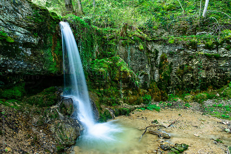 Small Waterfall inside green forest in spring by Peter Wey for Stocksy United