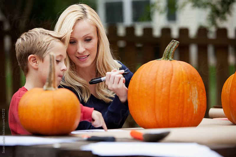 Pumpkins: Mother and Child Work on Jack-O-Lantern Face by Sean Locke for Stocksy United