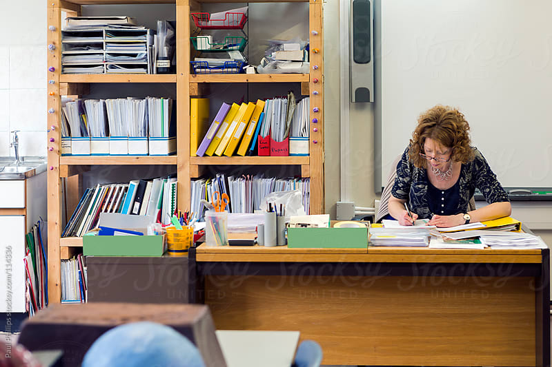 Classroom with teacher sitting behind her desk preparing for her class by Paul Phillips for Stocksy United