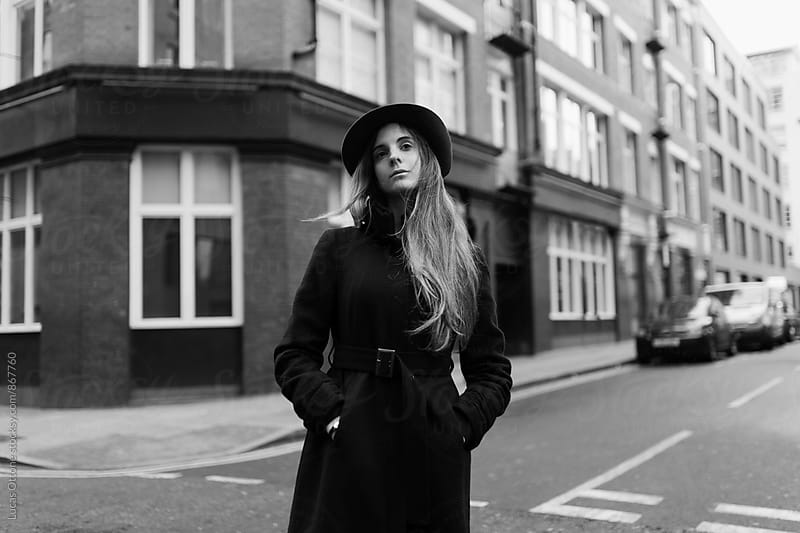 Young elegant woman in the street with hat and coat by Lucas Ottone for Stocksy United