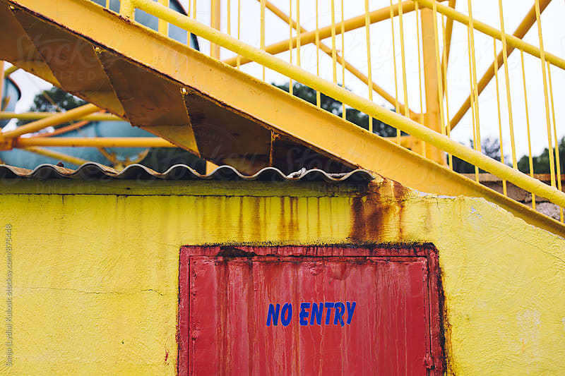 No entry sign in blue colour on red door and yellow wall by Sanja (Lydia) Kulusic for Stocksy United