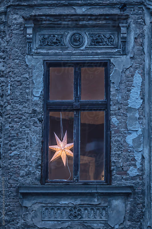 old facade, early  morning, New Year's window with modern lighting, star by Igor Madjinca for Stocksy United