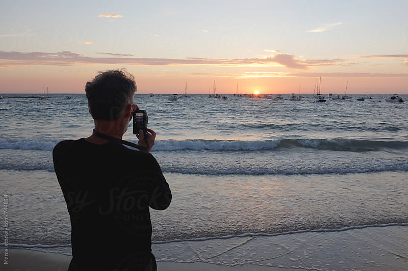 Man photographing the sunset at sea by Marcel for Stocksy United