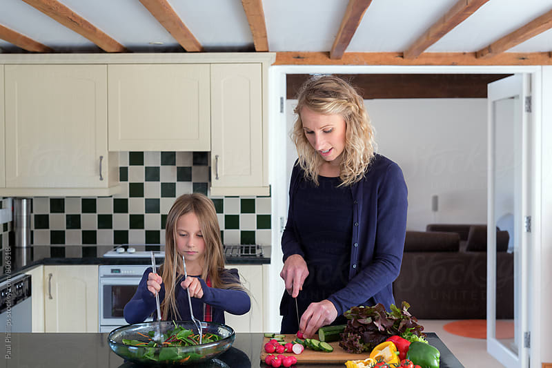 Daughter helping her mother to prepare lunch by Paul Phillips for Stocksy United