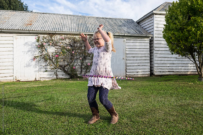 Cute little girl with specs playing with hula hoop by Rowena Naylor for Stocksy United