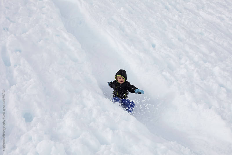 Boy kicks up powder at the end of a slide down a snowy embankment by Carleton Photography for Stocksy United