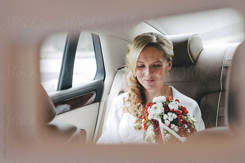 happy smiling blonde freckled bride in a rearview mirror in a car by Leander Nardin for Stocksy United
