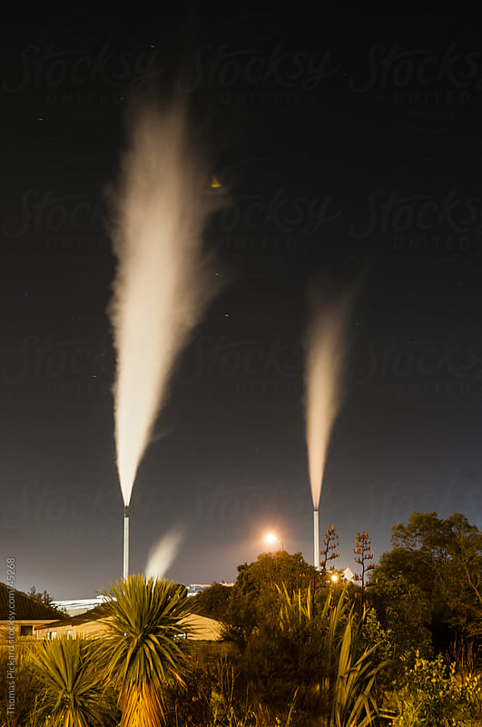Industrial chimney stacks and suburban housing, New Zealand. by Thomas Pickard Photography Ltd. for Stocksy United