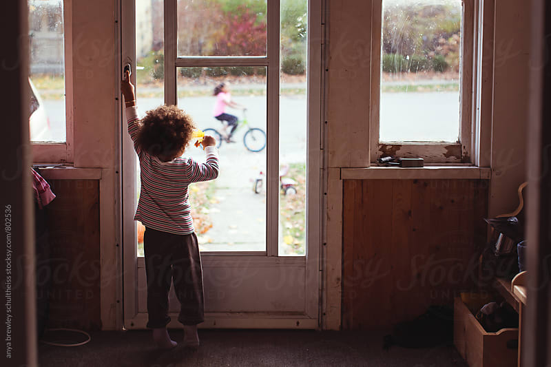 Toddler girl standing in a darkened room looking outward through a window at a girl riding a bicycle by anya brewley schultheiss for Stocksy United