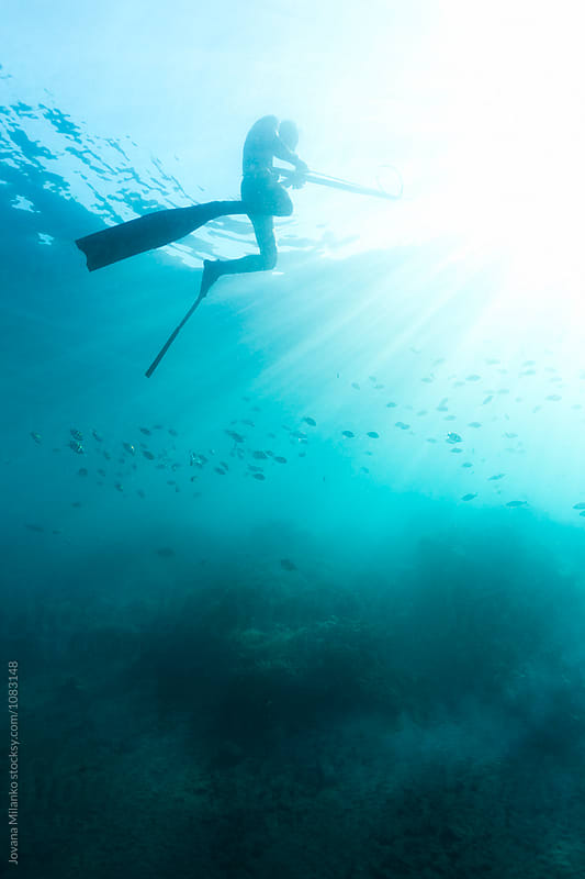 Spear fisherman hovering in blue water of Bali by Jovana Milanko for Stocksy United