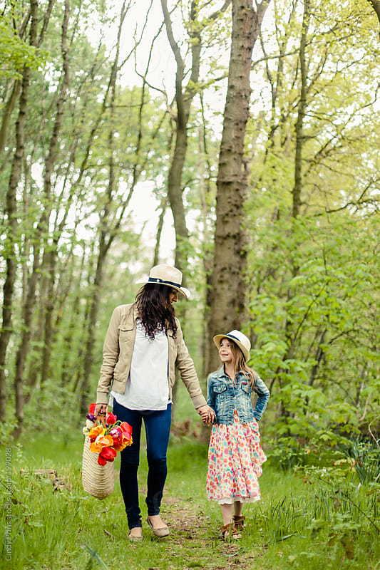 Mother and daughter walking through the forest after picking tulips by Cindy Prins for Stocksy United