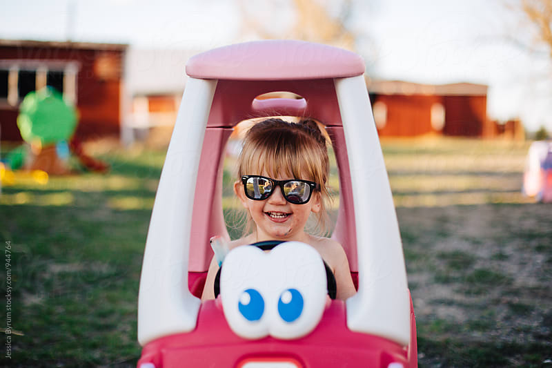 Toddler girl smiling in pink toy car by Jessica Byrum for Stocksy United