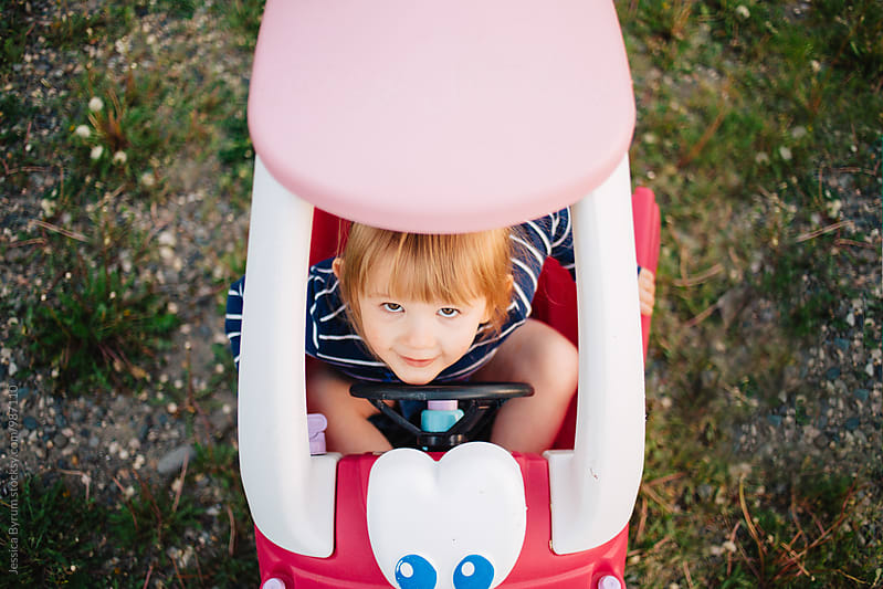 Toddler girl in a pink toy car looking up at the camera. by Jessica Byrum for Stocksy United