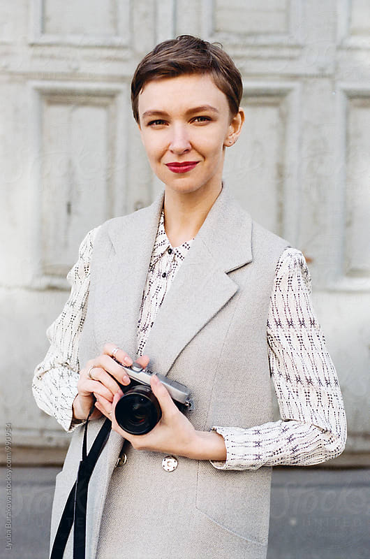 Woman holding a photo camera by Lyuba Burakova for Stocksy United
