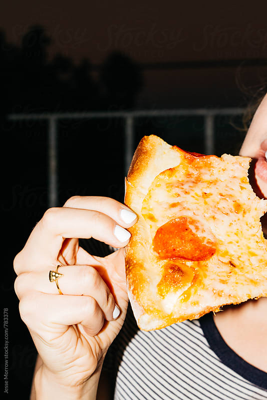 young female holding and eating pizza looking away from camera by Jesse Morrow for Stocksy United