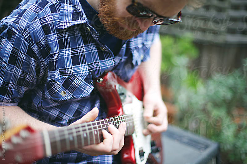 man playing guitar in backyard by Natalie JEFFCOTT for Stocksy United
