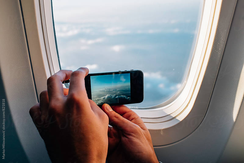 Man taking pictures with mobile phone from airplane by Marko Milovanović for Stocksy United